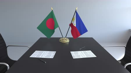 ondertekening : Flags of Bangladesh and Philippines and papers on the table. Negotiations and signing an international agreement. Conceptual 3D animation Stockvideo