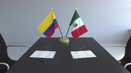 colômbia : Flags of Colombia and Mexico and papers on the table. Negotiations and signing an international agreement. Conceptual 3D animation