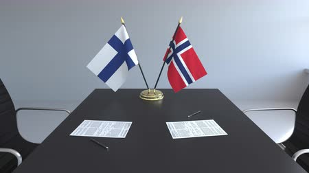 ondertekening : Flags of Finland and Norway and papers on the table. Negotiations and signing an international agreement. Conceptual 3D animation Stockvideo