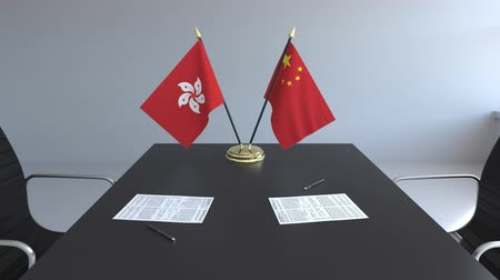 assinatura : Flags of Hong Kong and China and papers on the table. Negotiations and signing an international agreement. Conceptual 3D animation