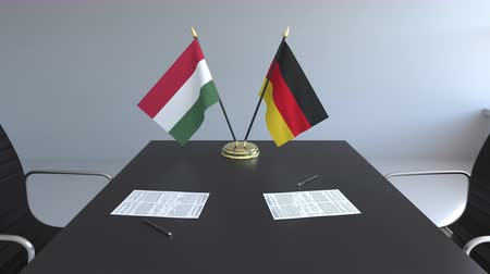assinatura : Flags of Hungary and Germany and papers on the table. Negotiations and signing an international agreement. Conceptual 3D animation Vídeos