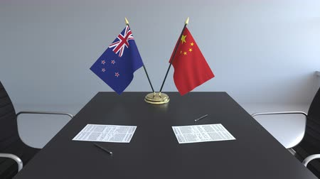 nowa zelandia : Flags of New Zealand and China and papers on the table. Negotiations and signing an international agreement. Conceptual 3D animation