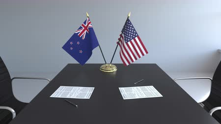 nowa zelandia : Flags of New Zealand and the United States and papers on the table. Negotiations and signing an international agreement. Conceptual 3D animation