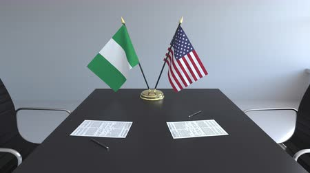 nigeria flag : Flags of Nigeria and the United States and papers on the table. Negotiations and signing an international agreement. Conceptual 3D animation