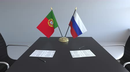 diplomatie : Drapeaux du Portugal et de la Russie et papiers sur la table. Négociations et signature d'un accord international. Animation 3D conceptuelle