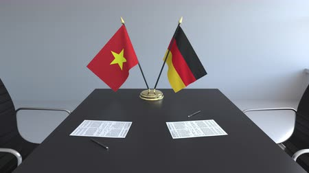 csapatmunka : Flags of Vietnam and Germany and papers on the table. Negotiations and signing an international agreement. Conceptual 3D animation