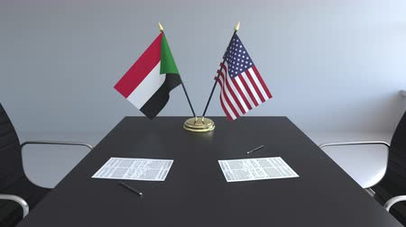 soedan : Flags of Sudan and the United States and papers on the table. Negotiations and signing an international agreement. Conceptual 3D animation