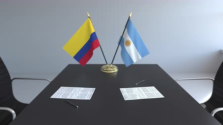 colômbia : Flags of Colombia and Argentina and papers on the table. Negotiations and signing an international agreement. Conceptual 3D animation