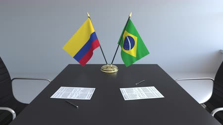 Колумбия : Flags of Colombia and Brazil and papers on the table. Negotiations and signing an international agreement. Conceptual 3D animation Стоковые видеозаписи