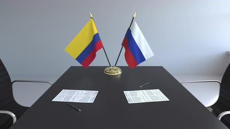 colômbia : Flags of Colombia and Russia and papers on the table. Negotiations and signing an international agreement. Conceptual 3D animation