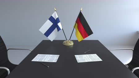 fince : Flags of Finland and Germany and papers on the table. Negotiations and signing an international agreement. Conceptual 3D animation