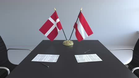 assinatura : Flags of Denmark and Austria and papers on the table. Negotiations and signing an international agreement. Conceptual 3D animation