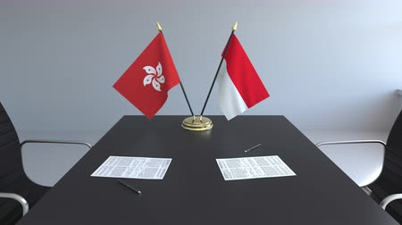 diplomatie : Drapeaux de Hong Kong et d'Indonésie et papiers sur la table. Négociations et signature d'un accord international. Animation 3D conceptuelle