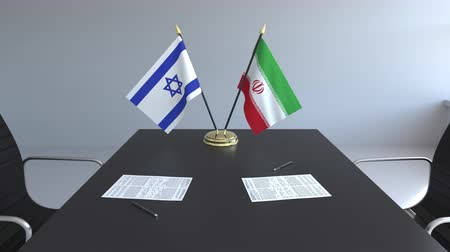 イラン : Flags of Israel and Iran and papers on the table. Negotiations and signing an international agreement. Conceptual 3D animation 動画素材
