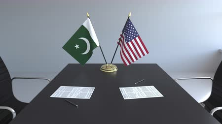 assinatura : Flags of Pakistan and the United States and papers on the table. Negotiations and signing an international agreement. Conceptual 3D animation