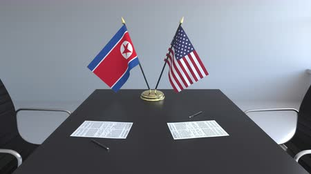 лидер : Flags of North Korea and the United States and papers on the table. Negotiations and signing an international agreement. Conceptual 3D animation