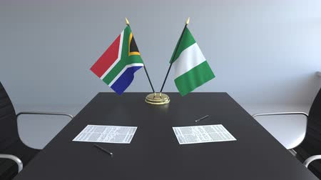 nigeria flag : Flags of South Africa and Nigeria and papers on the table. Negotiations and signing an international agreement. Conceptual 3D animation