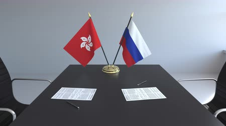 diplomatie : Drapeaux de Hong Kong et de la Russie et papiers sur la table. Négociations et signature d'un accord international. Animation 3D conceptuelle