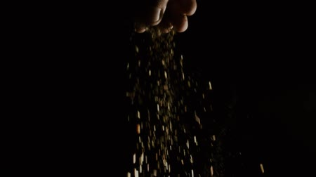 csip : Slow motion shot of pouring spice from the hand against black background Stock mozgókép