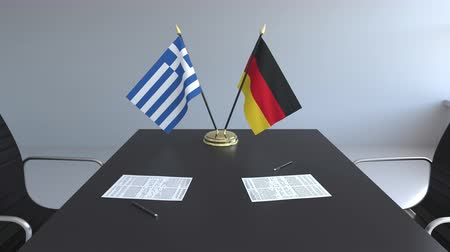 greek : Flags of Greece and Germany and papers on the table. Negotiations and signing an international agreement. Conceptual 3D animation