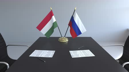 assinatura : Flags of Hungary and Russia and papers on the table. Negotiations and signing an international agreement. Conceptual 3D animation Vídeos
