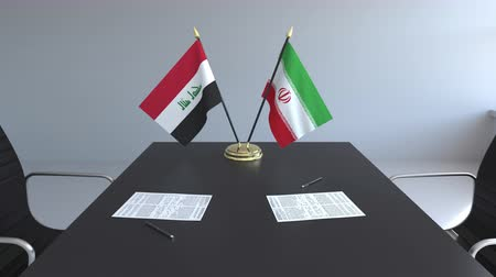 membro : Flags of Iraq and Iran and papers on the table. Negotiations and signing an international agreement. Conceptual 3D animation