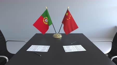 assinatura : Flags of Portugal and China and papers on the table. Negotiations and signing an international agreement. Conceptual 3D animation