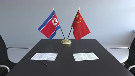 corée du nord : Flags of North Korea and China and papers on the table. Negotiations and signing an international agreement. Conceptual 3D animation
