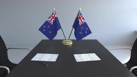 nowa zelandia : Flags of New Zealand and papers on the table. Negotiations and signing an agreement. Conceptual 3D animation