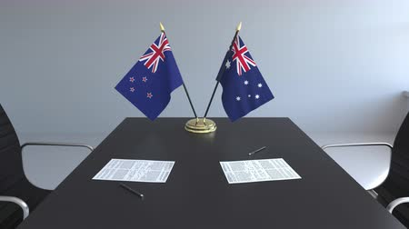 nowa zelandia : Flags of New Zealand and Australia and papers on the table. Negotiations and signing an international agreement. Conceptual 3D animation Wideo