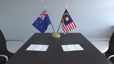 nowa zelandia : Flags of New Zealand and Malaysia and papers on the table. Negotiations and signing an international agreement. Conceptual 3D animation Wideo