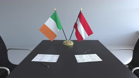 drapeau irlandais : Drapeaux de l'Irlande et de l'Autriche et papiers sur la table. Négociations et signature d'un accord international. Animation 3D conceptuelle