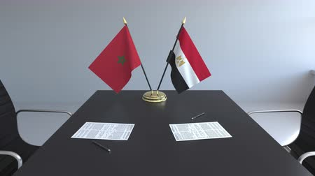 марокканский : Flags of Morocco and Egypt and papers on the table. Negotiations and signing an international agreement. Conceptual 3D animation