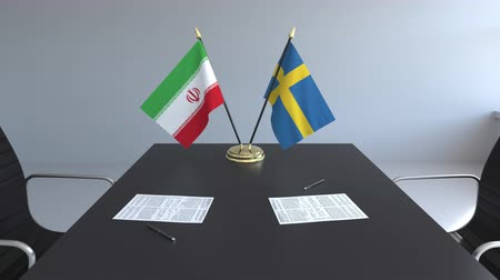İsveççe : Flags of Iran and Sweden papers on the table. Negotiations and signing an international agreement. Conceptual 3D animation Stok Video