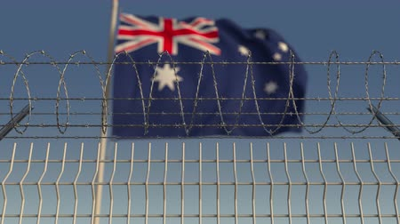 hapsedilme : Blurred waving flag of Australia behind barbed wire fence. Loopable 3D animation