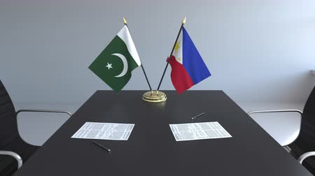 Пакистан : Flags of Pakistan and Philippines and papers on the table. Negotiations and signing an international agreement. Conceptual 3D animation