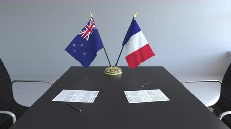 diplomatie : Drapeaux de Nouvelle-Zélande et de France et papiers sur la table. Négociations et signature d'un accord international. Animation 3D conceptuelle