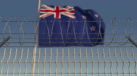 korlátozás : Defocused waving flag of New Zealand behind barbed wire fence. Loopable 3D animation