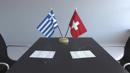 greek flag : Flags of Greece and Switzerland and papers on the table. Negotiations and signing an international agreement. Conceptual 3D animation Stock Footage