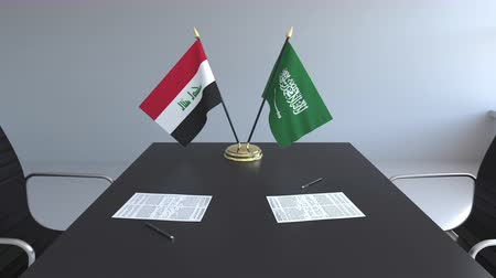 diplomatie : Drapeaux d'Irak et d'Arabie Saoudite et papiers sur la table. Négociations et signature d'un accord international. Animation 3D conceptuelle