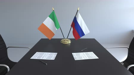 drapeau irlandais : Drapeaux de l'Irlande et de la Russie et papiers sur la table. Négociations et signature d'un accord international. Animation 3D conceptuelle