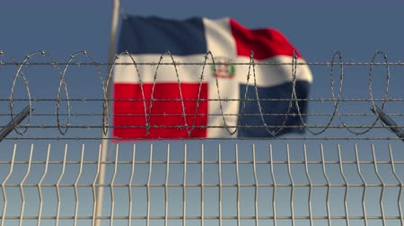hapsedilme : Blurred waving flag of the Dominican Republic behind barbed wire fence. Loopable 3D animation