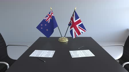 nowa zelandia : Flags of New Zealand and the United Kingdom and papers on the table. Negotiations and signing an international agreement. Conceptual 3D animation