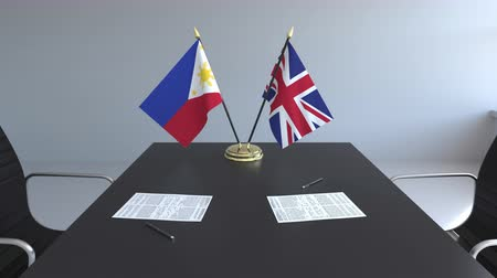 csapatmunka : Flags of Philippines and the United Kingdom and papers on the table. Negotiations and signing an international agreement. Conceptual 3D animation Stock mozgókép