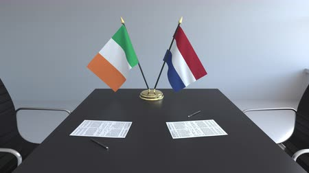 membro : Flags of Ireland and Netherlands and papers on the table. Negotiations and signing an international agreement. Conceptual 3D animation Vídeos