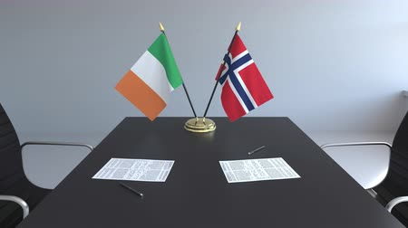 assinatura : Flags of Ireland and Norway and papers on the table. Negotiations and signing an international agreement. Conceptual 3D animation