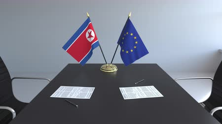 dprk : Flags of North Korea and the European Union and papers on the table. Negotiations and signing an international agreement. Conceptual 3D animation