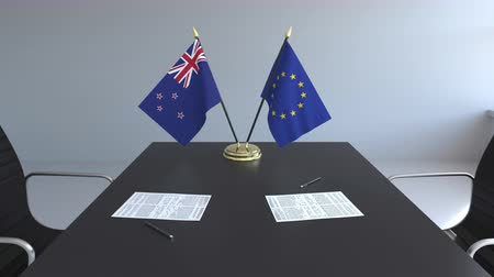assinatura : Flags of New Zealand and the European Union and papers on the table. Negotiations and signing an international agreement. Conceptual 3D animation