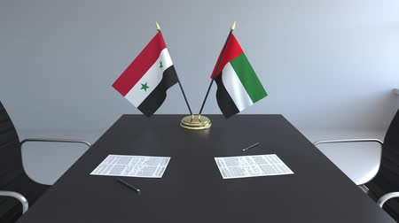 syrian : Flags of Syria and the UAE and papers on the table. Negotiations and signing an international agreement. Conceptual 3D animation