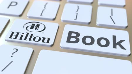 hilton : HILTON company logo and Book text on the keys of the computer keyboard, editorial conceptual animation Stock Footage